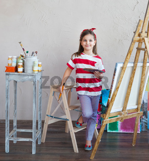 Little artist girl holding a paintbrush and looking over a canvas on an easel