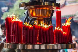 Candles burn in Longshan Buddhist temple in Taipei city Taiwan