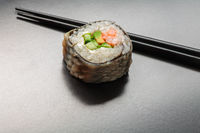 Hot sushi roll on a glossy black surface with blurred reflection and place for text