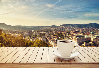 table with cup of coffee on city background