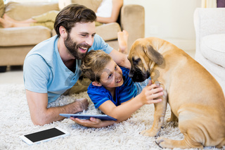 Father and son playing with a dog while using digital tablet