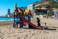 Alicante, Spain- January 8, 2016: Children playing in the playground on the Albufereta beach. This is one of the most popular holiday spot amongst local people of Alicante. Costa Blanca. Spain