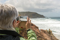 One Senior photographed with a smartphone the coast
