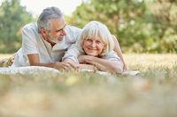 Paar Senioren in Liebe liegt entspannt im Gras