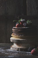 Breakfast in the wood : chocolate pancakes with strawberries, blackberries and castor sugar with old wooden doors in backround