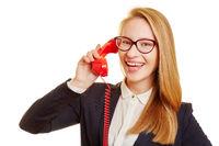 Geschäftsfrau telefoniert mit rotem Telefon