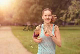 Hübsche Frau macht Jogging im Park mit Smartphone