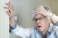 An elderly lady with a headache holds his hand to his forehead and braced on the door frame.