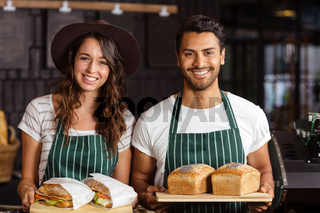 Smiling baristas holding bread and sandwiches