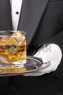 Butler holding whiskey glass on tray