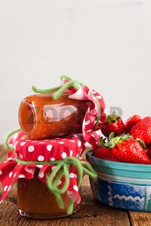 Einmachgläser mit Erdbeermarmelade und frische Erdbeeren