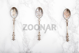 Old Vintage Dessert Spoons with Ornament on White Marble