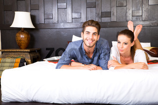 A young couple lying on the bed in an asian style hotel room