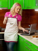 Beautiful young woman in the kitchen using a laptop