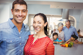 Portrait of happy couple with family preparing food in background