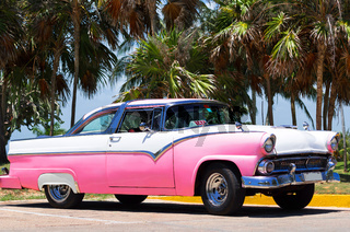 Rosa Carbiolet Oldtimer parkt am Strand von Havanna Kuba
