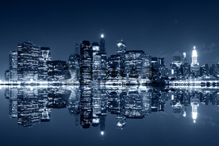 Manhattan at night with reflections on Harlem river