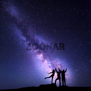 Milky Way. Night sky with silhouette of a happy family