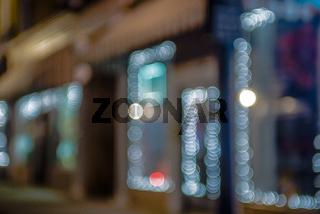 defocused storefront sidewalk lights at night
