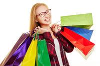 Lachende Frau beim Shopping mit Tüten