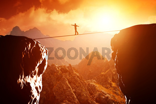 Man walking and balancing on rope over precipice in mountains at sunset. Concept of business