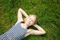 young girl lying on grass