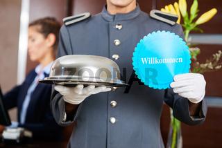 Hoteldiener hält Speiseglocke und Willkommen Schild