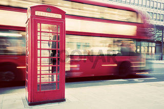 London, UK. Red telephone booth and red bus passing. Symbols of England.