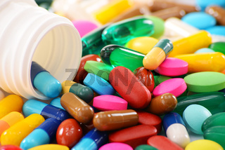 Composition with variety of drug pills and container.