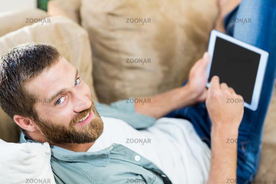 Portrait of man lying n sofa and using digital tablet