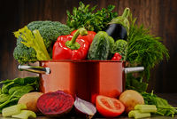 Composition with pot and raw vegetables.