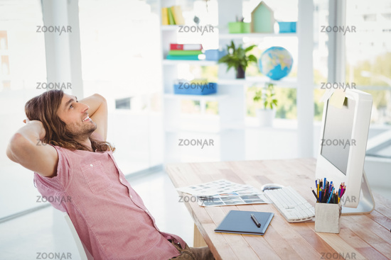Side view of hipster relaxing at computer desk