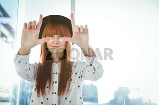 Smiling hipster woman do a framing with her hands