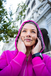 A woman wearing a pink jacket putting her headphones