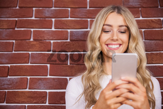 Beautiful blonde woman smiling and using smartphone