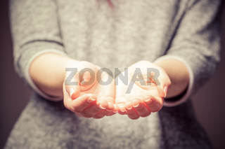 Light in young woman#39;s hands. Sharing, giving, offering, taking care, protection.