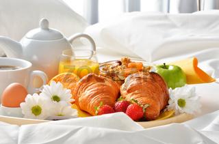 Breakfast tray in bed in hotel room.