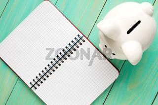 Piggy bank and open notebook.