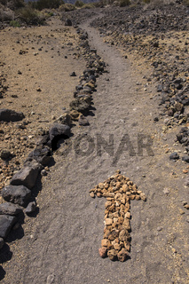 Arrow on the ground made from small stones on a walking route in the Las Canadas del Teide national park