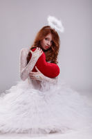 Nice young girl dressed as angel posing with heart