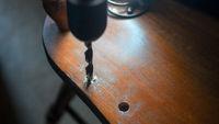 Drilling. Carpenter repairing old chair.