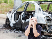 Crying upset man at arson fire burnt car vehicle