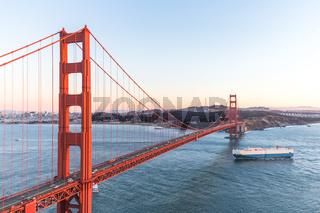 cargo ship crossing through gold gate bridge at sunset