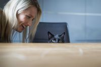 A young blond woman communicates with a black cat