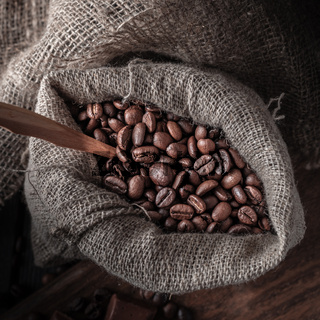 Bag of coffee beans on a dark background.