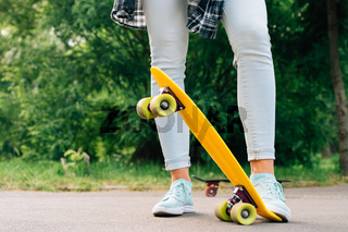 Women's legs in jeans and sneakers on yellow skateboard closeup