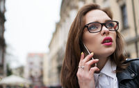 pretty woman in the city speaking using smartphone