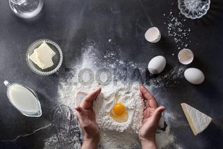 Woman#39;s hands knead dough on table with flour