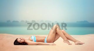 happy woman tanning in bikini over swimming pool