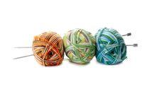 three melange ball of wool and knitting needles